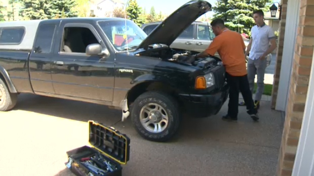 instaMek technician Jamez Burnink under the hood of a Ford Ranger on the driveway of a Calgary home