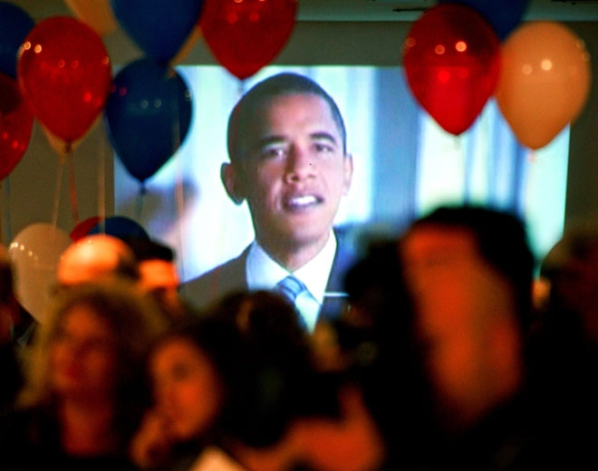 An image of the U.S. President-elect Barack Obama plays on the television, as people attend an election day event organized by the U.S. embassy in Skopje, Macedonia, early Wednesday, Nov. 5, 2008. (AP / Boris Grdanoski)