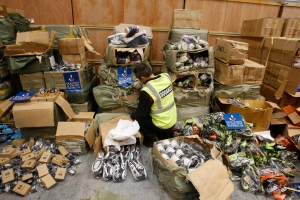 A French Customs officer searches boxes of counterfeit sport shoes, during a press conference to present seized merchandise in Le Havre, western France, Thursday, Dec. 8, 2011.(AP Photo/Remy de la Mauviniere)