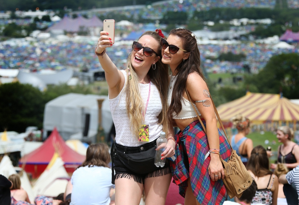 Music fans take selfies on the hill overlooking the tents at Glastonbury Music Festival on Thursday, June 25, 2015. (Joel Ryan/Invision)