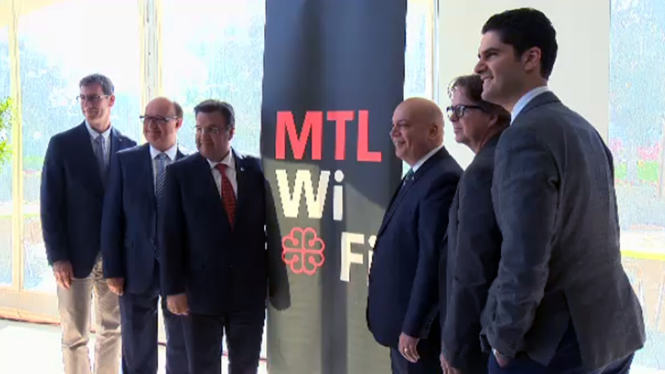 Denis Coderre, Robert Poeti, and other politicians surround a sign for MTLWiFI