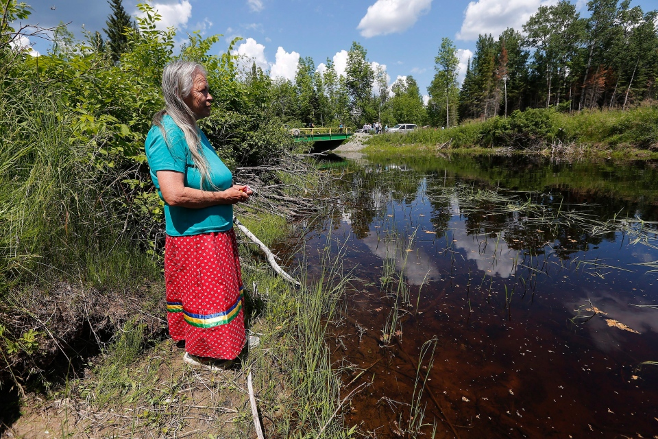 Community elder Grace Redsky from Shoal Lake 40 First Nation performed a water healing ceremony at a man-made channel made to support Winnipeg's water system which has cut them off from the mainland Thursday, June 25, 2015. (John Woods / THE CANADIAN PRESS)