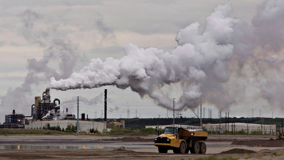 A dump truck works near the Syncrude oil sands extraction facility near the town of Fort McMurray, Alberta on Sunday June 1, 2014. (Jason Franson/THE CANADIAN PRESS)