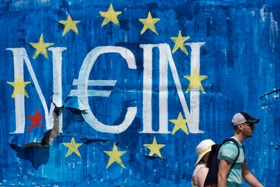 Tourists walks past a graffiti made by street artist N_Grams that read 'NO' in German but also 'YES, IN' in Greek language in Athens, on Sunday, June 28, 2015. (AP/Petros Giannakouris)
