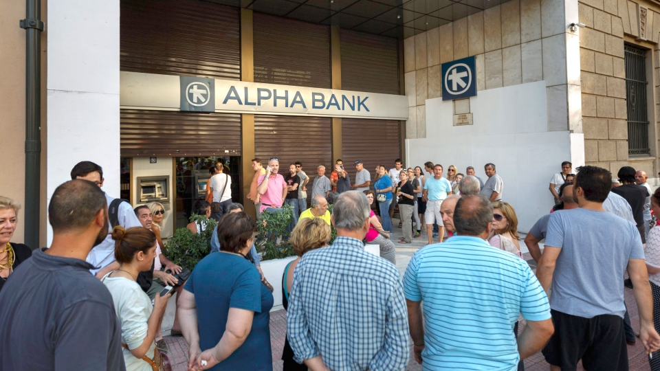 People stand in a queue to use ATM cash machine of a bank in central Athens on Sunday, June 28, 2015. (AP / Daniel Ochoa de Olza)