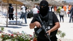A hooded Tunisian police officer stands guard ahead of the visit of top security officials of Britain, France, Germany and Belgium at the scene of Friday's shooting attack in front of the Imperial Marhaba hotel in the Mediterranean resort of Sousse, Tunisa, Monday, June 29, 2015. (AP / Abdeljalil Bounhar)