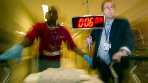Dr. Richard Swartz  holds a 'stroke clock' as he runs a gurney down a hall at Sunnybrook Hospital in Toronto, on Thursday, October 28, 2010. (THE CANADIAN PRESS/Frank Gunn)