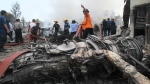 Firefighters and military personnel work at the site where an Air Force cargo plane crashed in Medan, North Sumatra, Indonesia on June 30, 2015. (AP / Gilbert Manullang)