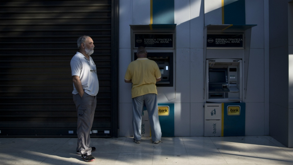 A man receives money from an ATM machine outside a national bank branch, in Athens, on June 30, 2015. (AP / Petros Giannakouris)