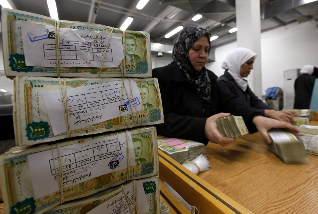 Syrian employees stack currency at central bank