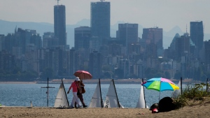 Women shield themselves from the sun on Jericho Beach in Vancouver, on Monday, June 29, 2015. (THE CANADIAN PRESS/Darryl Dyck)