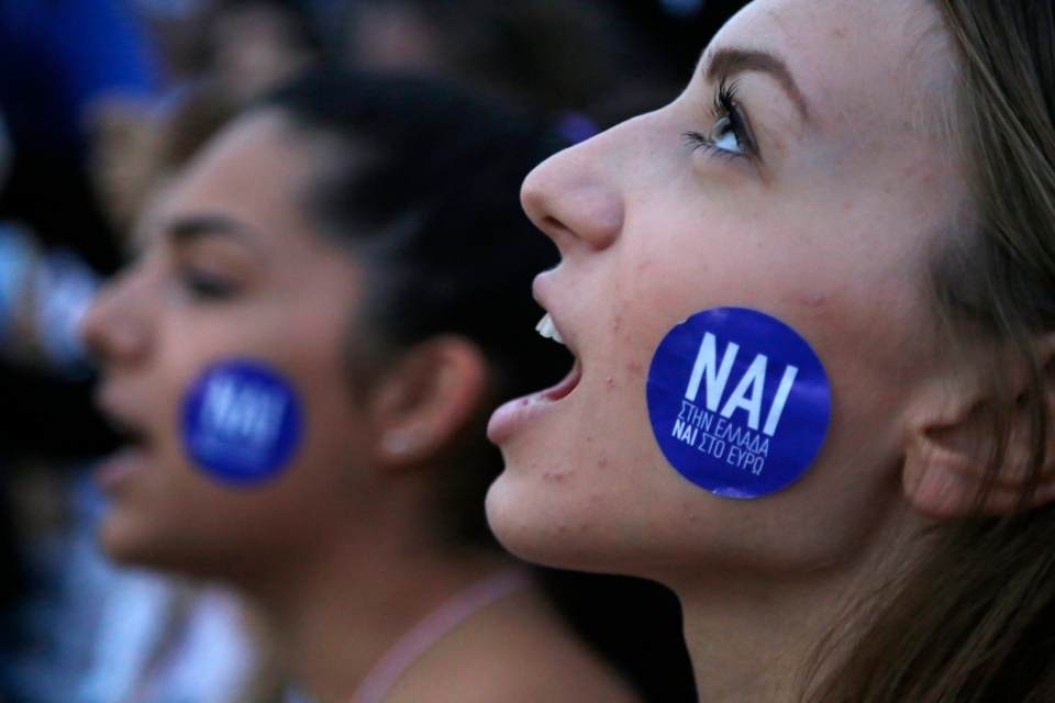 A demonstrator shouts slogans as the sticker on her cheek reading ''YES to Greece, Yes to Euro'' during a rally organized by supporters of the YES vote for the upcoming referendum in front of the Greek Parliament in Athens, Tuesday, June 30, 2015. (AP / Petros Karadjias)