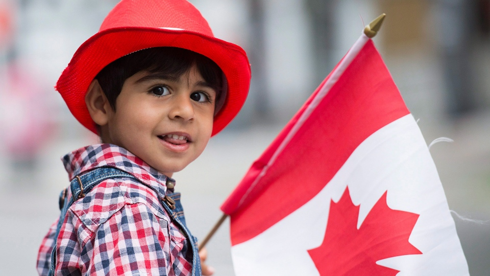 Three year old Sam Kashfi smiles as he watches the annual Canada Day parade in Montreal, Wednesday, July 1, 2015. (Graham Hughes / THE CANADIAN PRESS)