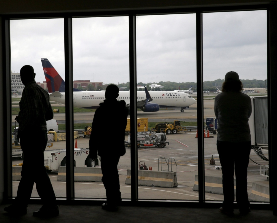 In this photo taken Tuesday, April 14, 2015, Delta Airlines passengers watch as a Delta plane taxis at Atlanta's Hartsfield International Airport in Atlanta. (AP/Charles Rex Arbogast)