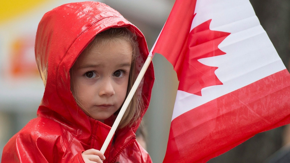 A young girl holds a flag during the annual Canada Day parade in Montreal, Wednesday, July 1, 2015. (Graham Hughes / THE CANADIAN PRESS)