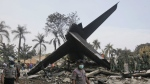 Rescuers search for victims at the site where an Indonesian air force transport plane crashed in Medan, North Sumatra, Indonesia on July 1, 2015. (AP / Binsar Bakkara)