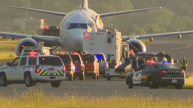 Police respond to a bomb threat that forced an Edmonton-to-Toronto flight to land in Calgary on July 1, 2015.