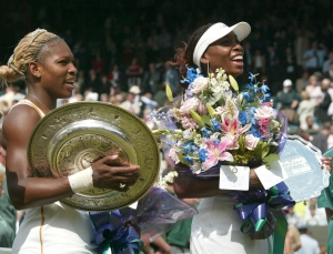 In this July 6, 2002 photo, Serena Williams, left, holds her trophy after defeating her sister Venus, right, to win the Women's Singles final on the Centre Court at the All England Lawn Tennis Championships in Wimbledon, London. (AP / Ted S.Warren)