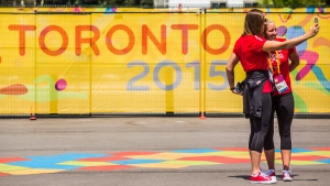 """Canadian water polo athletes Monika Eggens, left, and Jacqueline Kohli take a """"selfie"""" in the square inside the Pan American Games athletes village in Toronto on July 3, 2015. (Mark Blinch / THE CANADIAN PRESS)"""