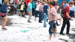 A severe thunderstorm dumped heavy rain and hail on the Calgary Stampede grounds resulting in people navigating through accumulations in Calgary, Alberta on July 4 , 2015. (Larry MacDougal / THE CANADIAN PRESS)