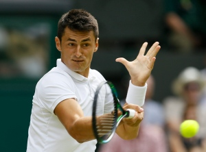 Bernard Tomic of Australia returns a ball to Novak Djokovic of Serbia during their singles match at the All England Lawn Tennis Championships in Wimbledon, London on July 3, 2015. (Kirsty Wigglesworth / AP Photo)