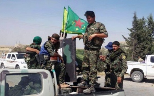 In this photo provided by the Kurdish fighters of the People's Protection Units, which has been authenticated based on its contents and other AP reporting, Kurdish fighters of the YPG, sit on their pickup in the town of Ein Eissa, north of Raqqa city, Syria, Tuesday, June 23, 2015. (The Kurdish fighters of the People's Protection Units via AP)