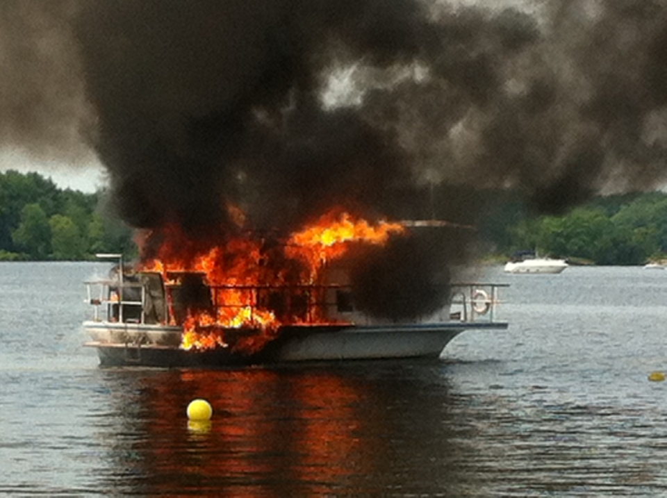 Flames can be seen coming from a house boat at the Starport Marina in Port Severn, Ont. on Sunday, July 5, 2015. (Sara Reimer)