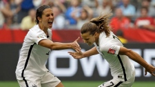 United States' Tobin Heath, right, celebrates with Carli Lloyd, left, after Heath scored a goal against Japan during the second half of the FIFA Women's World Cup soccer championship in Vancouver, British Columbia, Canada, Sunday, July 5, 2015. (AP /Elaine Thompson)