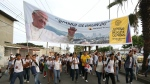 Pilgrims hold a banner of Pope Francis as they walk towards Samanes Park to take part in a vigil in Guayaquil, Ecuador on July 5, 2015. (AP / Fernando Vergara)