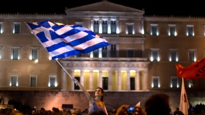 A supporter of the No vote waves a Greek flag in front of the parliament after the results of the referendum at Syntagma square in Athens. (AP / Emilio Morenatti)