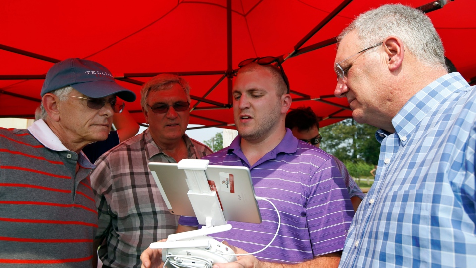 Mike Geske, left, from Sikeston, Mo., Bob Bowman, from DeWitt, Iowa, with Kevin Skunes, right, from Arthur, N.D., watch the display during a drone demonstration at a farm and winery on  June 11, 2015 in Cordova, Md. (AP / Alex Brandon)