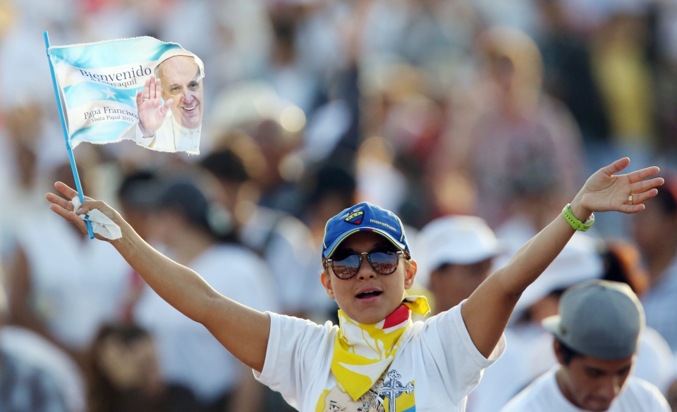 A woman spreads her arms, waving a flag with an image of Pope Francis in a crowd of thousands waiting in the Samanes Park, in Guayaquil, Ecuador on Monday, July 6, 2015. (AP / Fernando Vergara)