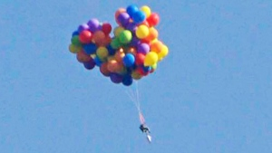 A person is seen in a lawn chair, strapped to dozens of helium balloons, in this photo snapped by Tom Warne and posted on Twitter.