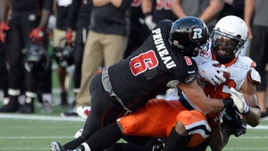 Ottawa REDBLACKS' Antoine Pruneau (6) and Jerrell Gavins (24) stop B.C. Lions fullback Rolly Lumbala during second half CFL action in Ottawa on Saturday July 4, 2015. (Adrian Wyld/THE CANADIAN PRESS)
