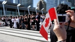 A woman takes a photograph while holding a Canadian flag as a group of 61 new Canadians take the oath of citizenship during a citizenship ceremony held as part of Canada Day celebrations in Vancouver, on Wednesday, July 1, 2009. (Darryl Dyck/The Canadian Press)