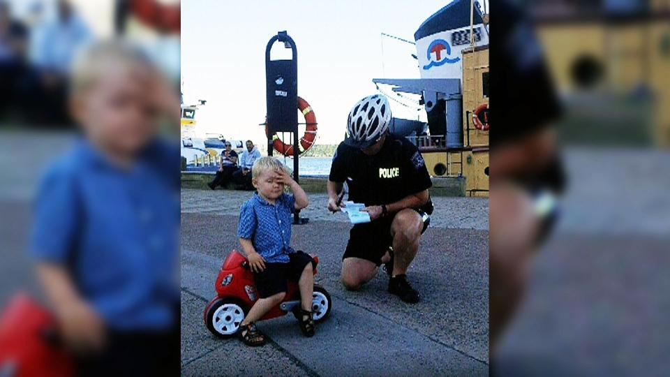 Halifax Regional Police Cst. Shawn Currie tickets Declan Tramley, 3, on Halifax pier.