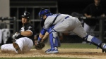 Chicago White Sox's Jose Abreu, left, slides into home plate safely on a Melky Cabrera RBI double as Toronto Blue Jays catcher Russell Martin tries to apply the tag during the eighth inning of a baseball game in Chicago on July 6, 2015. (AP / Paul Beaty)