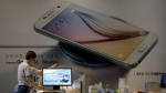 Employees of Samsung Electronics Co. check the products near an advertisement of Samsung Electronics' Galaxy S6 smartphone at a Samsung Electronics shop in Seoul, South Korea on July 7, 2015. (AP / Lee Jin-man)