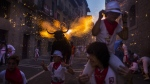 """A flaming fake bull known as a """"Toro de fuego"""" runs after revelers during the 2015 San Fermin fiestas in Pamplona, Spain, Monday, July 6, 2015. (AP / Andres Kudacki)"""