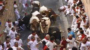 Participants run ahead of fighting bulls from Santo Domingo street during the running of the bulls at the San Fermin Festival, in Pamplona, Spain on July 7, 2015. (AP / Alvaro Barrientos)