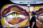 A woman walks past a graffiti in Athens, on Tuesday, July 7, 2015. (AP / Petros Giannakouris)