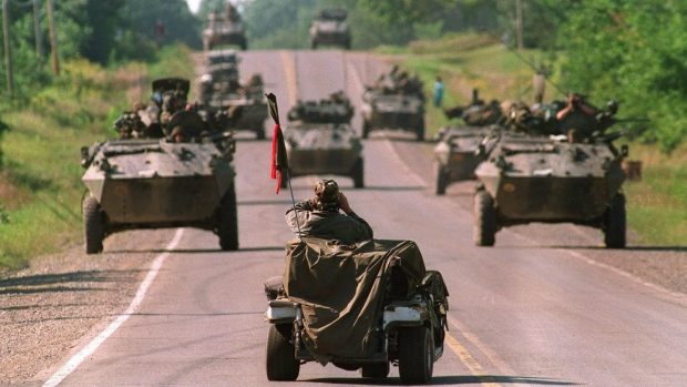 Mohawk warrior watches armoured vehicles