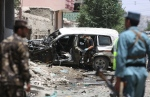 Afghan security personnel inspect a damaged vehicle at the site of a suicide attack that targeted a NATO convoy in Kabul, Afghanistan, Tuesday, July 7, 2015. (AP / Rahmat Gul)