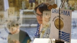A tourist looks at a storefront display of jewelry made from old drachma coins in the historic Plaka district of central Athens, Tuesday, July 7, 2015. Greece is struggling to restart talks with bailout creditors following an impasse that has threatened Greece's place in the euro. (AP / Petros Karadjias)