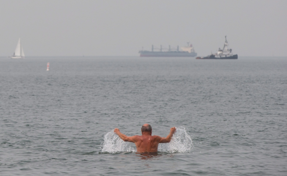 A man swims in English Bay as smoke from wildfires across the province fills the air in Vancouver on Monday July 6, 2015. (Darryl Dyck / THE CANADIAN PRESS)