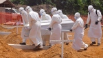 Health workers carry a body of a person that they suspected died form the Ebola virus at a new graveyard on the outskirts of Monrovia, Liberia on March 11, 2015. (AP / Abbas Dulleh)