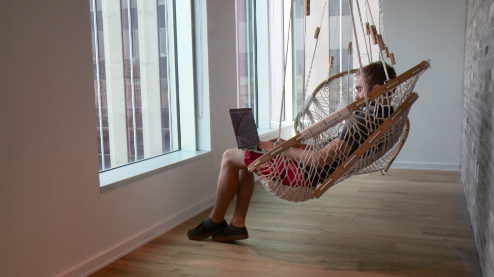 A worker swings from a hammock chair at Shopify in Ottawa, July 7, 2015