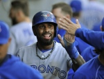 Toronto Blue Jays' Jose Reyes celebrates with teammates in the dugout after scoring on a Jose Bautista groundout during the first inning of a baseball game against the Chicago White Sox Tuesday, July 7, 2015 in Chicago. (AP / Paul Beaty)