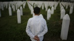 Srebrenica massacre survivor Nedzad Avdic, 37, walks through the graves of those killed in the massacre and buried at the Memorial Center in the Srebrenica suburb of Potocari, 150 kilometre northeast of Sarajevo on June 27, 2015. (AP / Amel Emric)