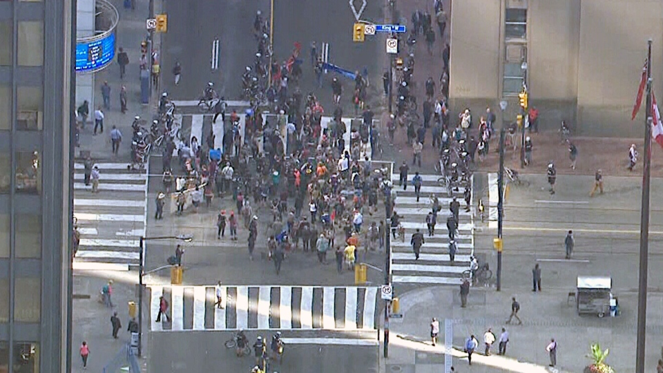 Protesters are seen blocking traffic in downtown Toronto to demonstrate against climate and economic conference in the city on July 8, 2015.